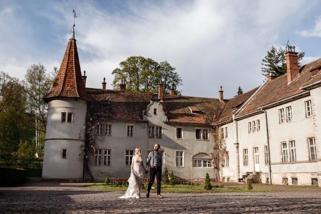Hermosa pareja de novios está caminando cerca del antiguo castillo, antigua arquitectura restaurada, antiguo edificio, antigua casa exterior, vintage palacio al aire libre. amor romántico en calle de ambiente vintage