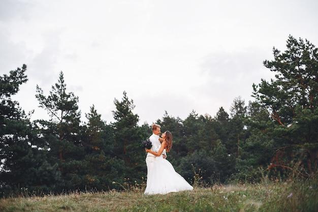 Hermosa pareja de novios en un campo de verano