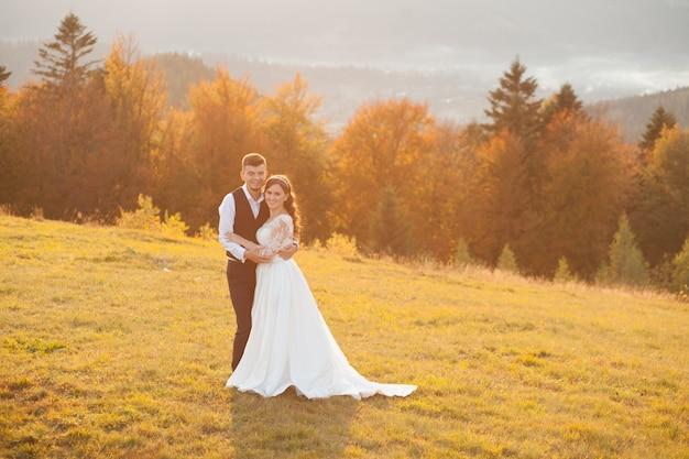 Hermosa pareja, novios, enamorados en el fondo de las montañas. el novio con un hermoso traje y la novia con un vestido blanco de lujo. pareja de novios está caminando