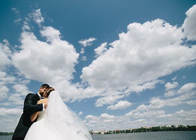 Hermosa pareja de novios en el fondo de cielo azul, agua