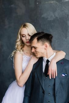 Hermosa pareja de novios. lujoso vestido de la novia y elegante traje del novio, sesión de fotos de estudio.