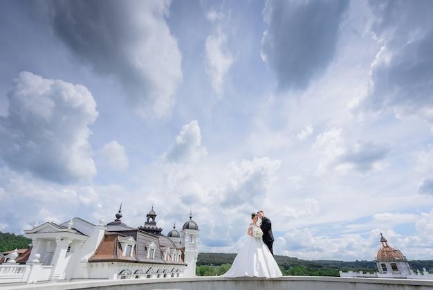 Hermosa pareja de novios está de pie cerca de la iglesia con hermoso cielo nublado