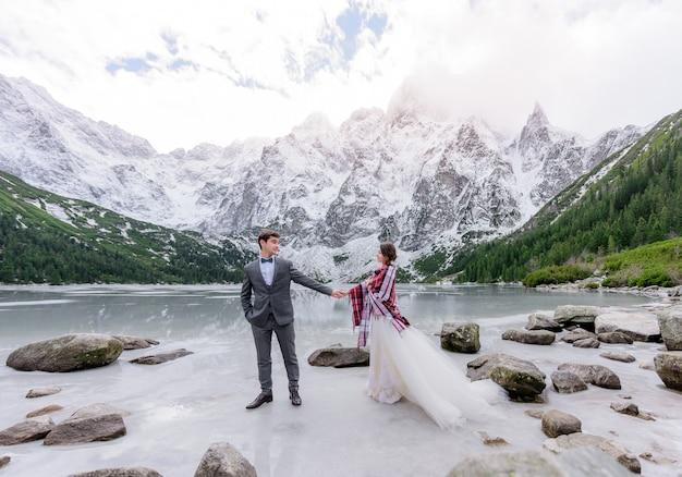 Hermosa pareja de novios está de pie sobre el hielo del lago congelado highland con increíbles paisajes de montaña de invierno