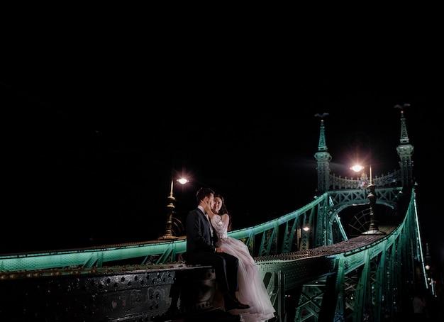 Hermosa pareja de novios está sentada en el puente iluminado en la noche oscura y besándose