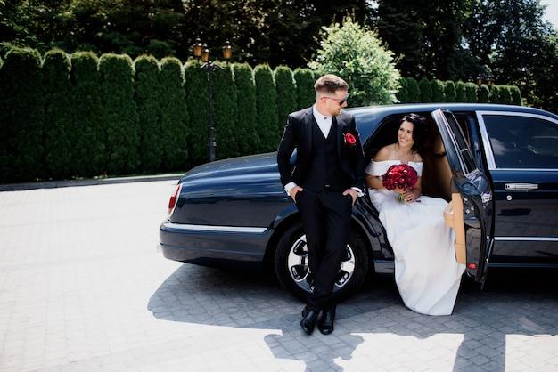 Hermosa pareja de novios está sonriendo en el automóvil negro en el día soleado, vestida con elegantes trajes de boda con ramo rojo
