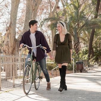 Hermosa pareja en el parque con bicicleta
