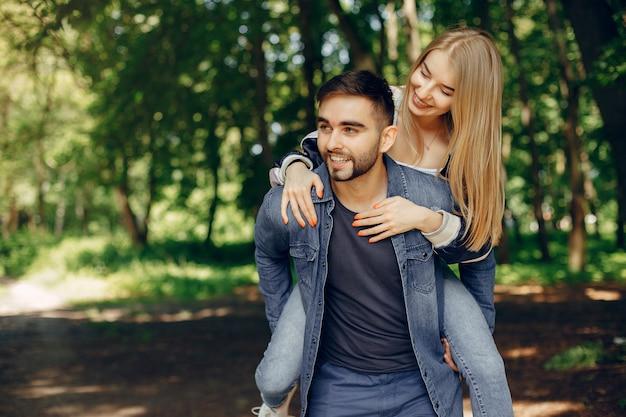 Hermosa pareja pasa tiempo en un bosque de verano