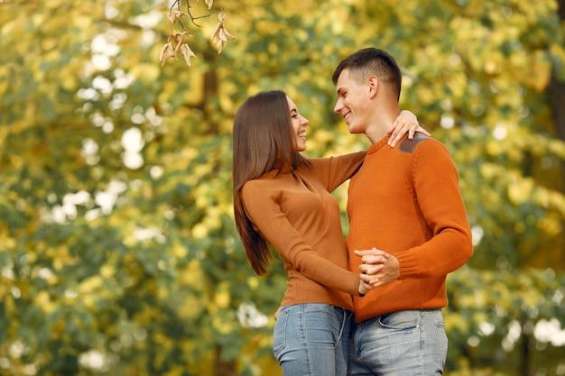 Hermosa pareja pasa tiempo en un campo de otoño