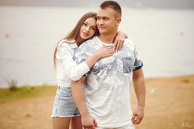Hermosa pareja pasa tiempo en un parque nublado de otoño