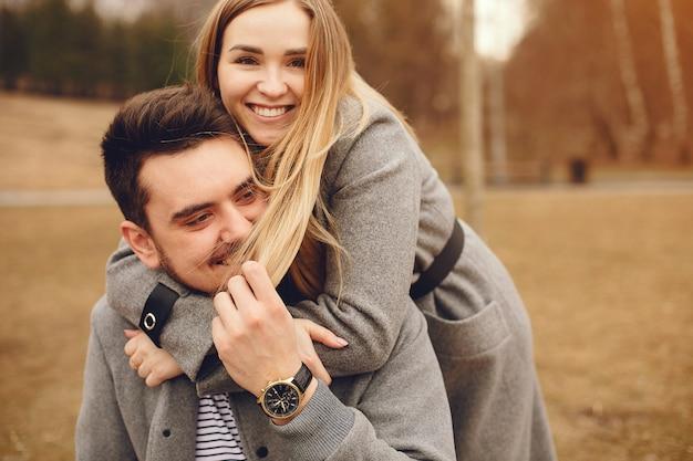 Hermosa pareja pasa tiempo en un parque de otoño