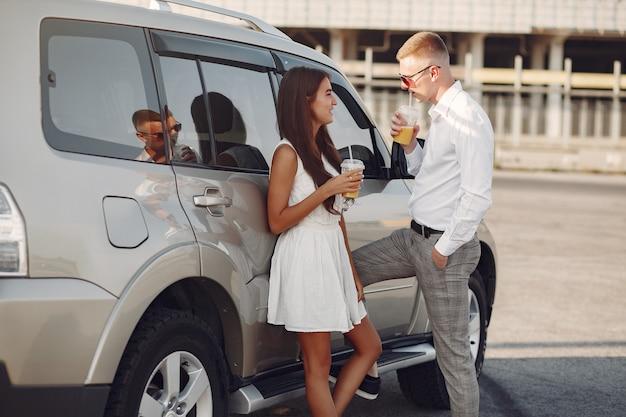 Hermosa pareja pasa tiempo en un parque de verano cerca de un automóvil
