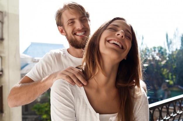 Hermosa pareja de pie en el balcón. hombre haciendo masaje a su novia.