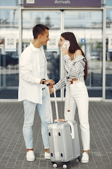 Hermosa pareja de pie cerca del aeropuerto