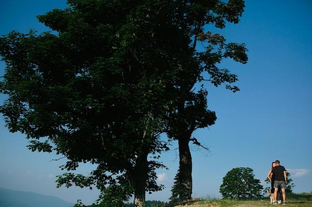 Hermosa pareja de pie sobre una colina y abrazándose suavemente