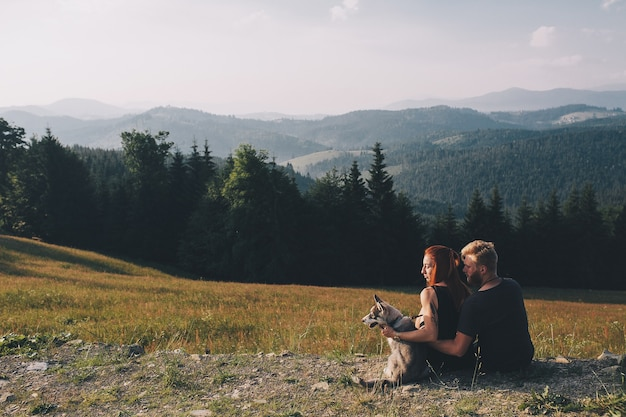 Hermosa pareja de pie sobre una colina y mira a lo lejos