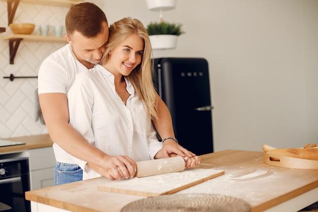 Hermosa pareja prepara comida en una cocina