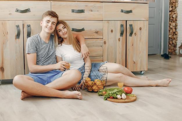 Hermosa pareja prepara comida en la cocina