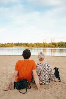 Hermosa pareja relajándose en la arena abrazándose y besándose mientras jugaba con su perro positivo