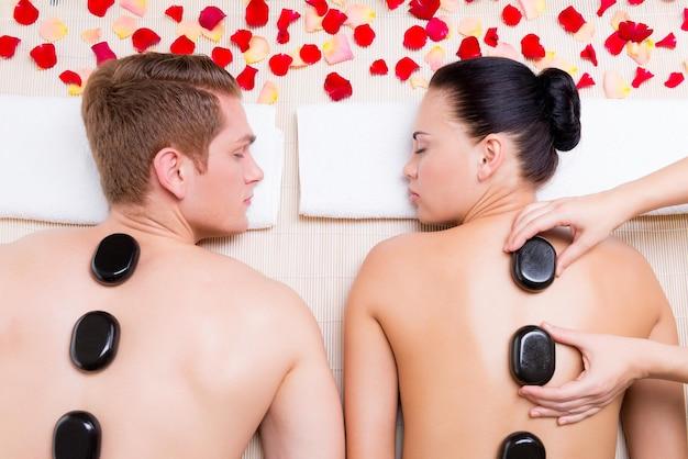 Hermosa pareja relajante en el salón de spa con piedras calientes en el cuerpo. terapia de tratamientos de belleza.