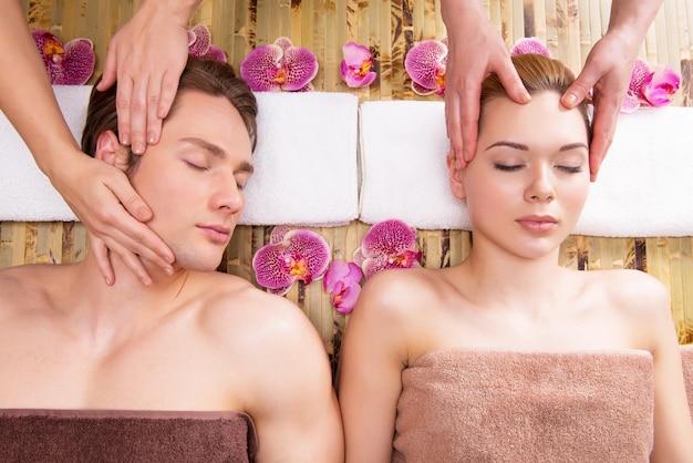 Hermosa pareja en un salón de spa disfrutando juntos de masaje de cabeza.