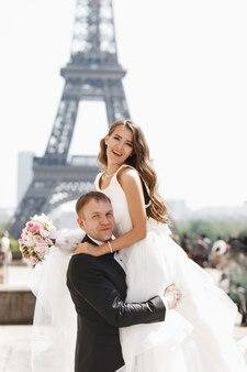 Hermosa pareja se divierte posando en la plaza antes de la torre eiffel en parís