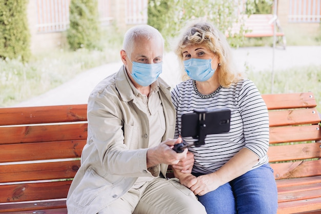 Hermosa pareja senior en el amor con máscara médica y haciendo selfie afuera