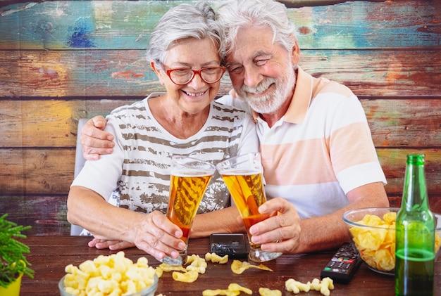 Hermosa pareja senior brindando con vasos de cerveza sentado en la mesa de madera. comiendo palomitas.