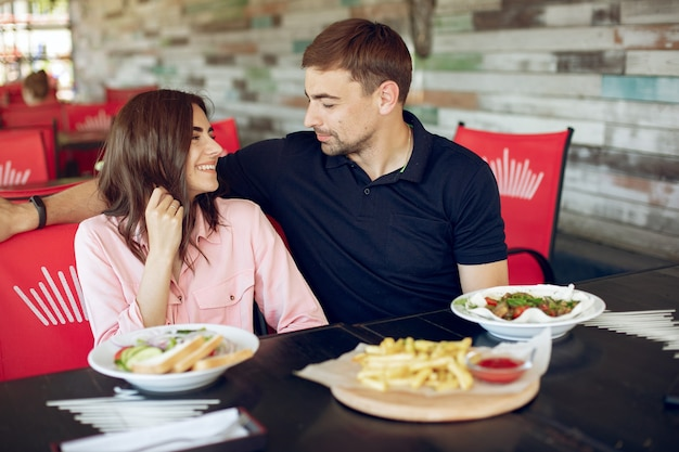 Hermosa pareja sentada en un café de verano