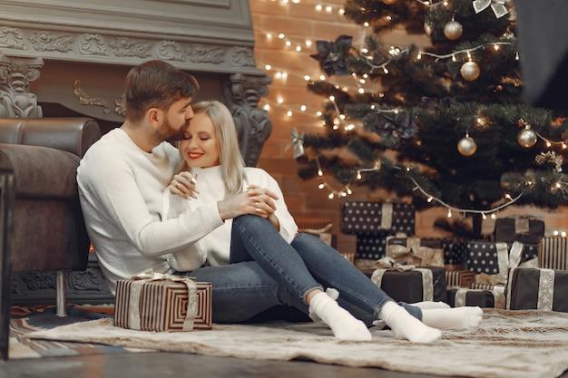 Hermosa pareja sentada en casa cerca del árbol de navidad