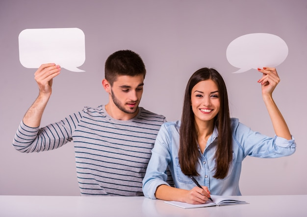 Hermosa pareja sentada en la mesa con burbuja de texto vacío.
