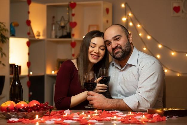 Hermosa pareja sentada en la mesa decorada con velas y pétalos de rosa, pasando la noche juntos