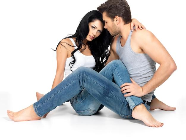 Hermosa pareja sexy enamorada en el espacio en blanco vestida con jeanse azul y camiseta blanca
