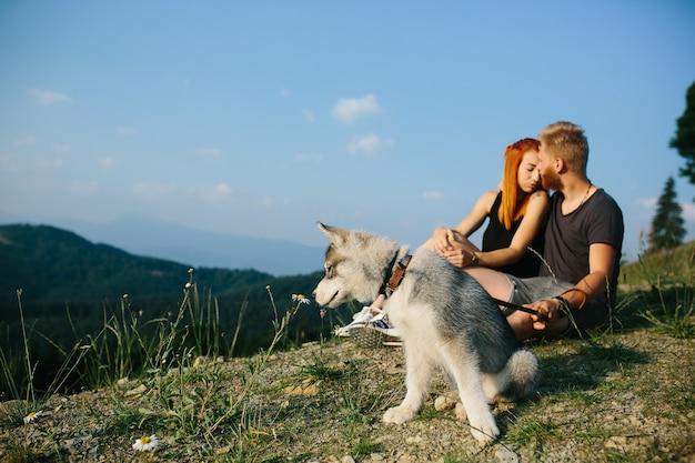 Hermosa pareja se sienta en una colina y abrazándose