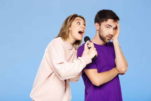Hermosa pareja sobre pared azul. chica cantando en micrófono hombre didpleased.