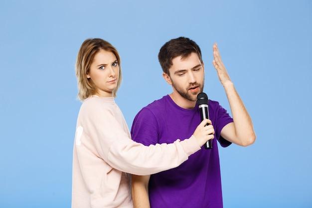 Hermosa pareja sobre pared azul hombre cantando en chica de micrófono disgustado.