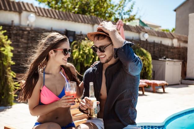 Hermosa pareja sonriendo, hablando, bebiendo cócteles, sentado cerca de la piscina