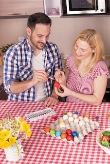 Hermosa pareja sonriendo y pintando los huevos de pascua