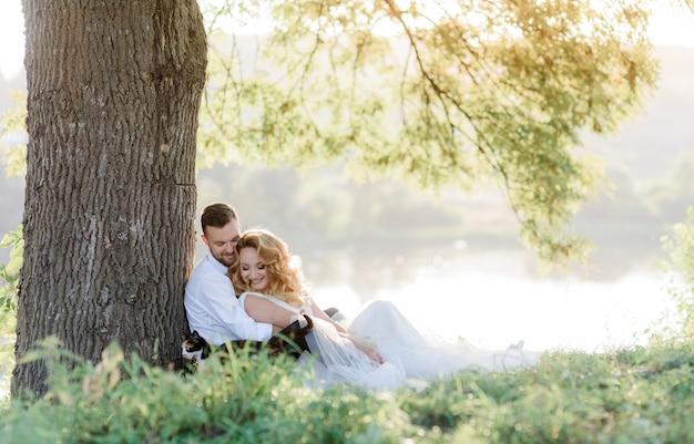 Hermosa pareja sonriente está sentada en la hierba verde cerca del árbol al aire libre, picnic romántico, familia feliz en el día soleado