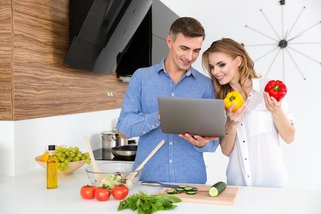 Hermosa pareja sonriente usando laptop y haciendo ensalada en la cocina