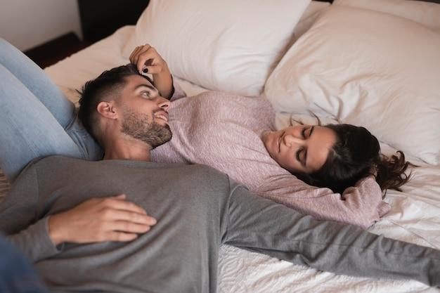 Hermosa pareja tendida en la cama