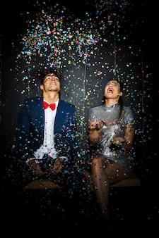 Hermosa pareja entre tirar confeti
