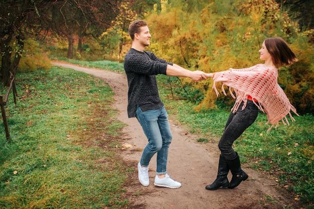 Hermosa pareja se toman de las manos y miran. se giran alrededor. la gente está en el prado. se ven felices.
