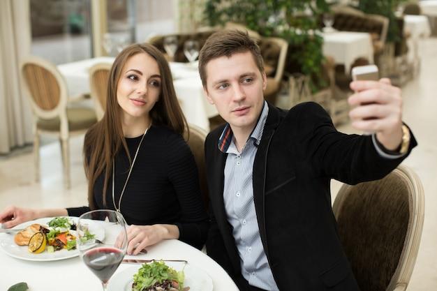 Hermosa pareja tomando selfie foto en un restaurante