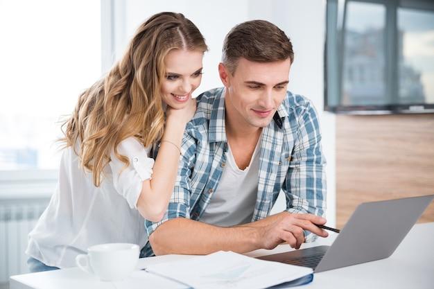 Hermosa pareja usando laptop y trabajando juntos