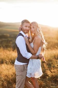 Hermosa pareja vestida en estilo boho abrazándose en el soleado campo de verano