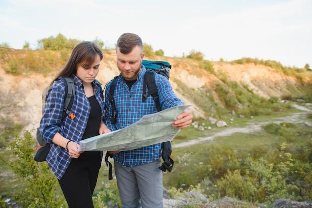Hermosa pareja de viajeros están buscando camino en el mapa de ubicación mientras están parados en una colina alta en un día soleado