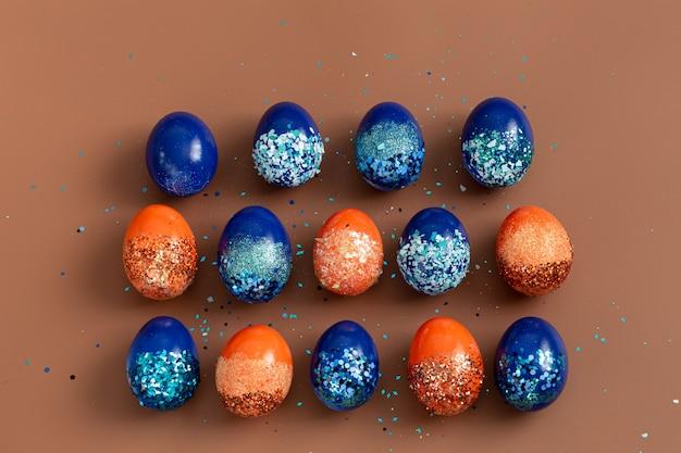 Hermosa pascua con huevos decorativos naranjas y azules en lentejuelas.