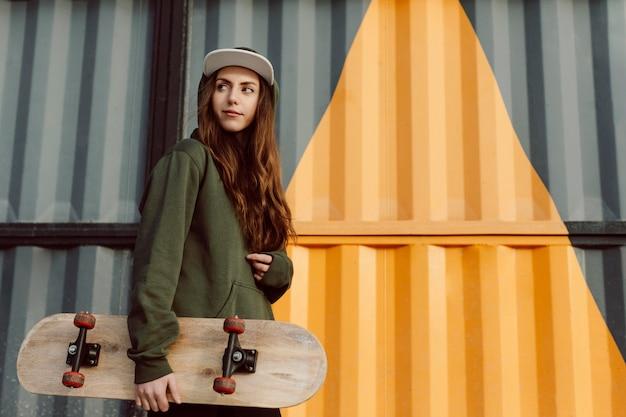 Hermosa patinadora sosteniendo su patineta
