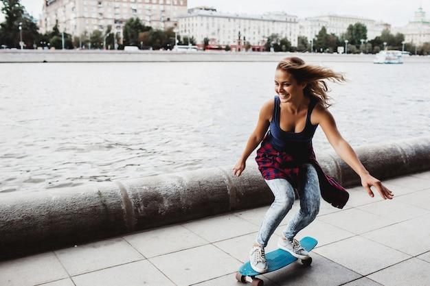 Hermosa patineta rubia en el paseo marítimo