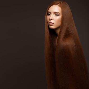 Hermosa pelirroja con un cabello perfectamente liso y un maquillaje clásico. cara de belleza